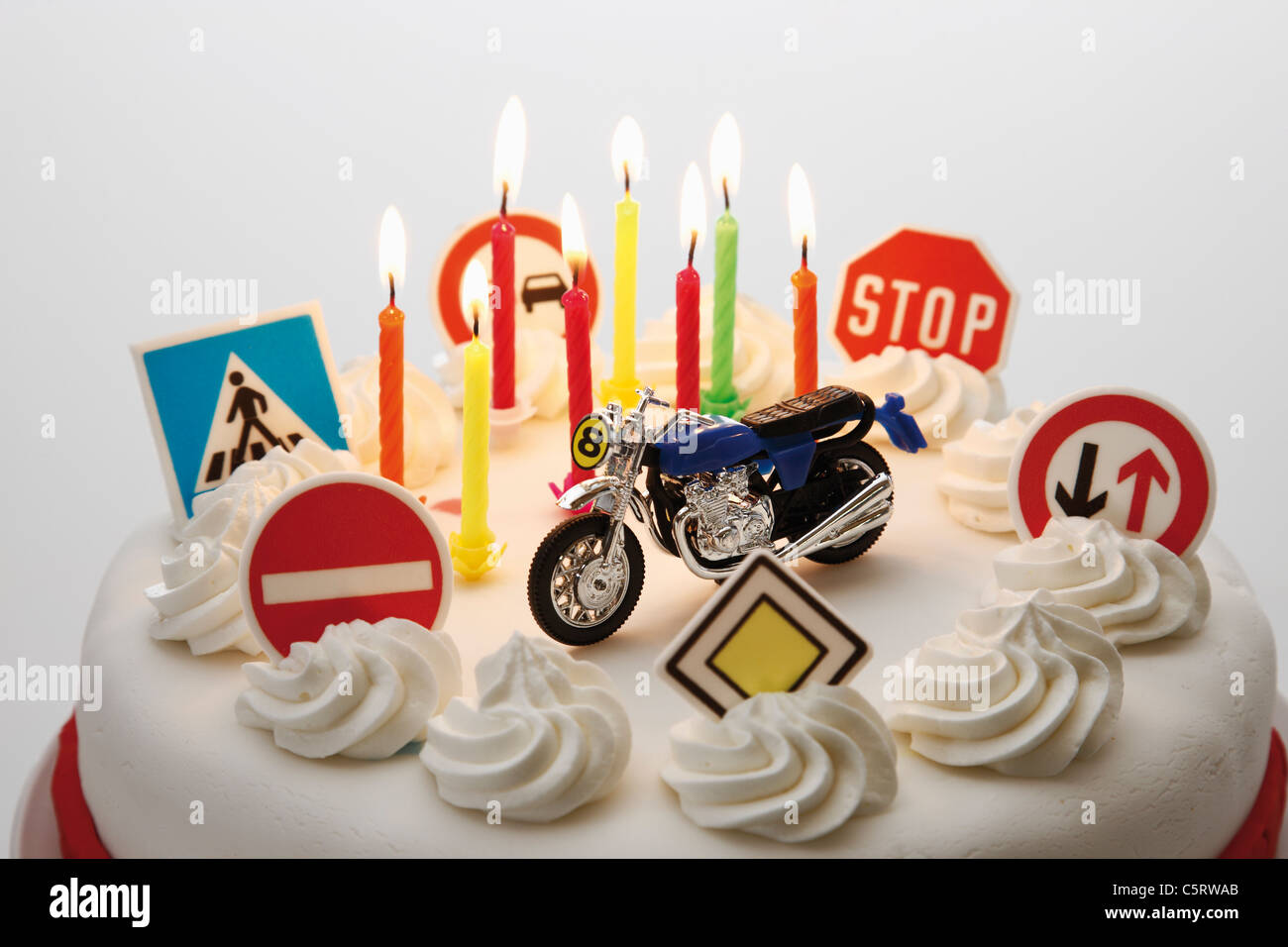 Fancy cake with road signs and toy motorbike, close-up - Stock Image
