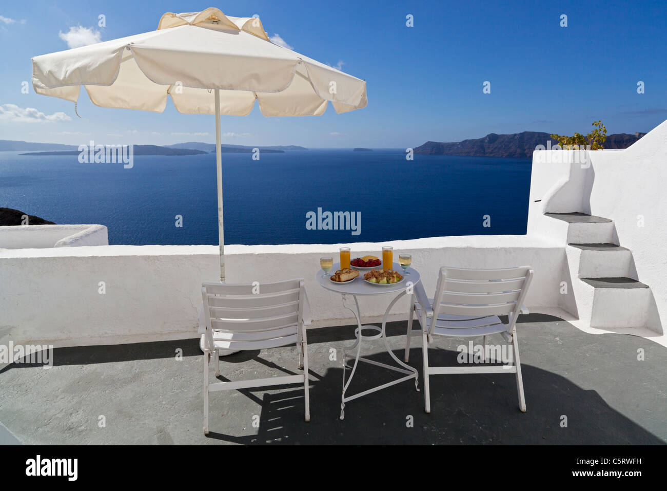 Greece, Cyclades,Thira, Santorini, Oia, Sunshade and furniture with food on terrace, blue sea in background - Stock Image