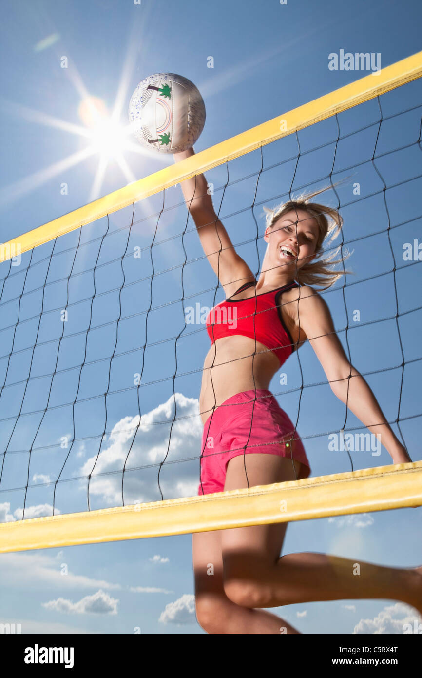 Germany, Bavaria, Mauern, Young woman taking shot in beach volleyball, smiling, portrait - Stock Image
