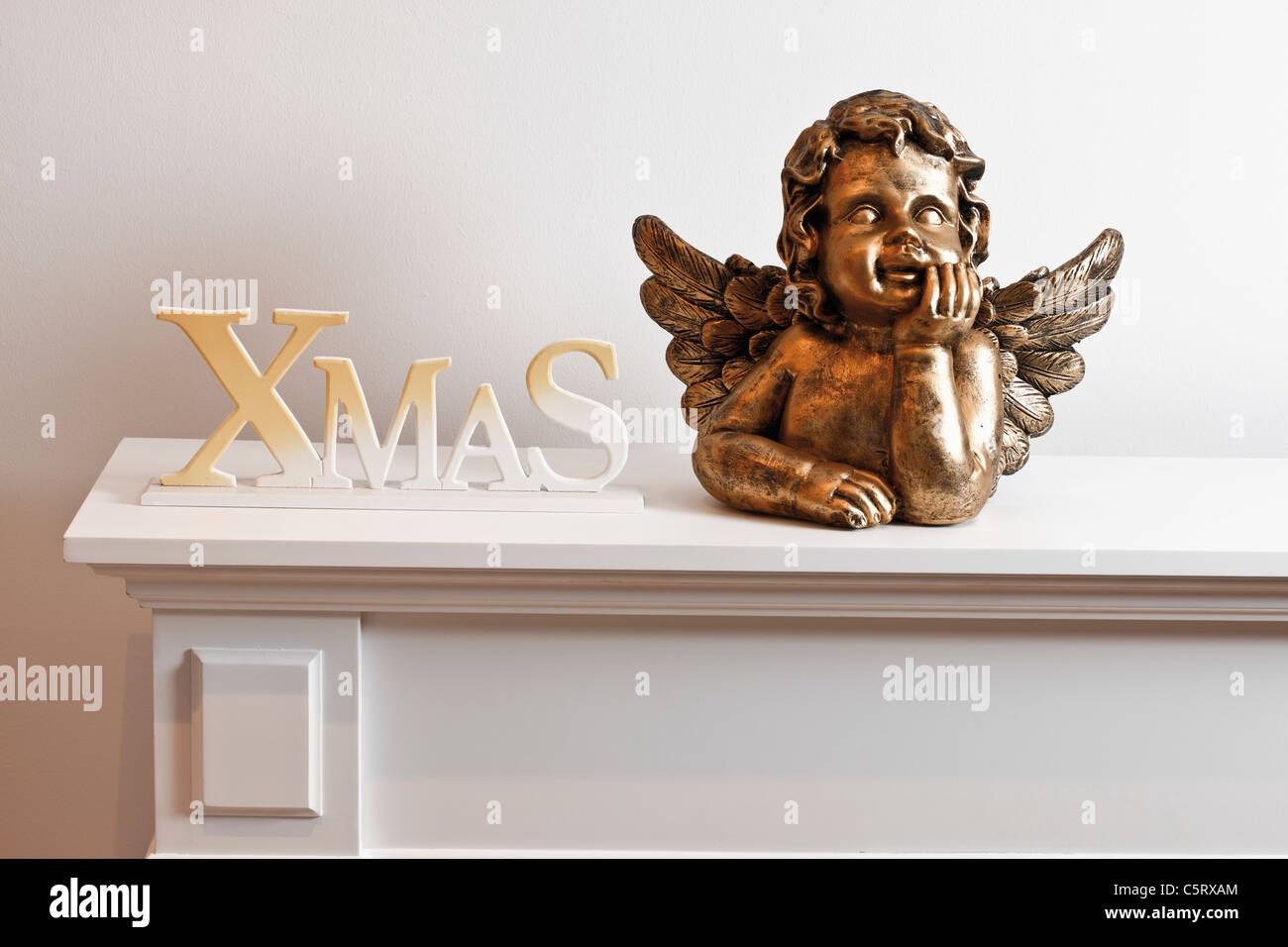 Angel figurine and decoration on shelf - Stock Image