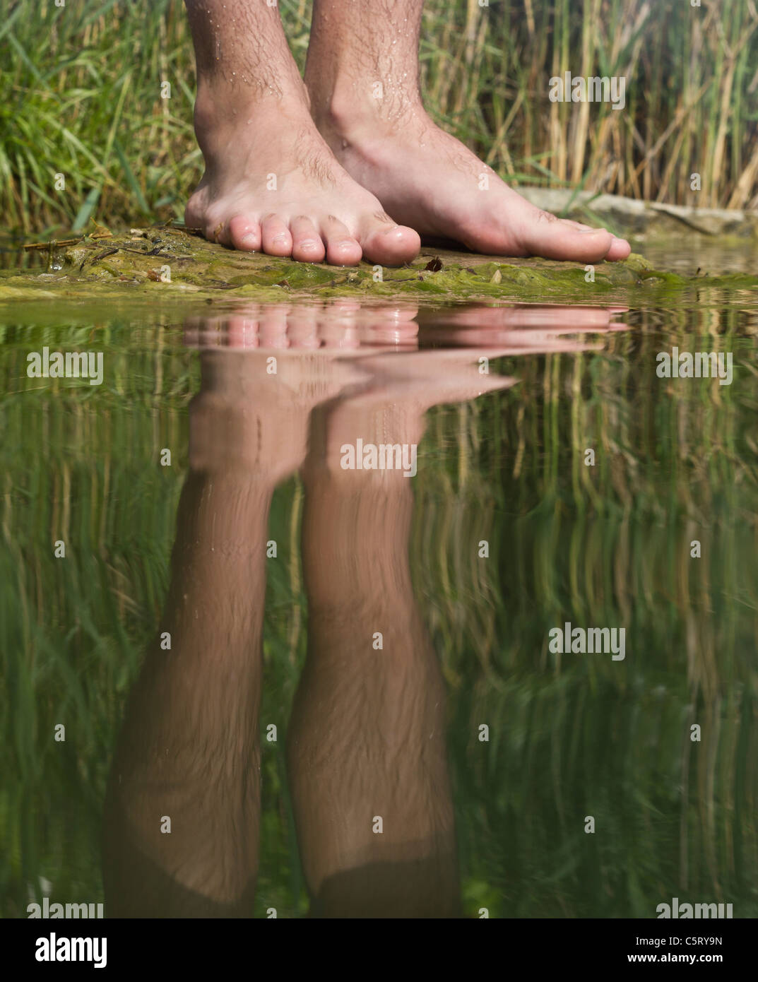 Austria, Vienna, Reflection of man's feet on lakeshore, close up - Stock Image