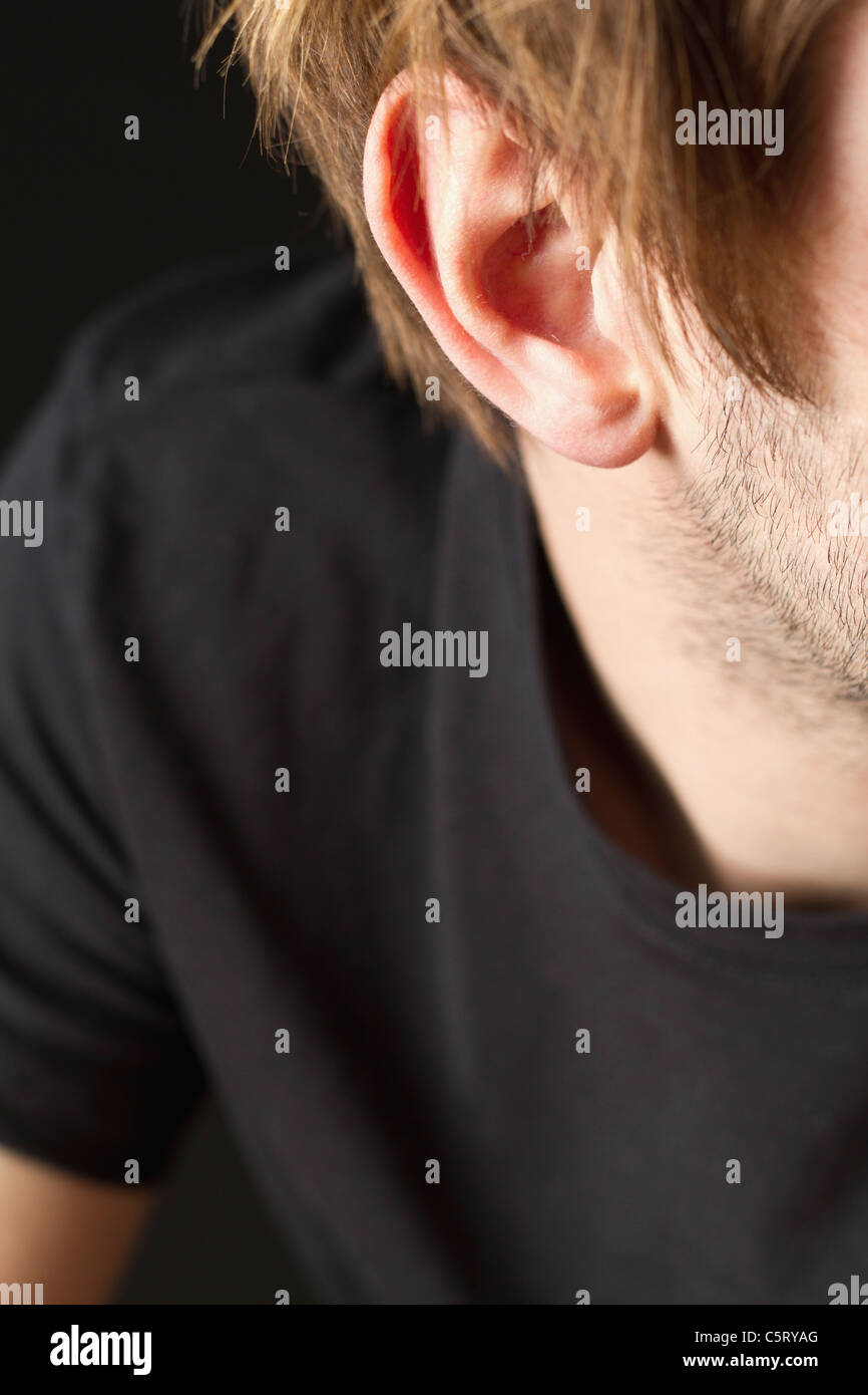 Ear of young man with stubble against black background, close up - Stock Image