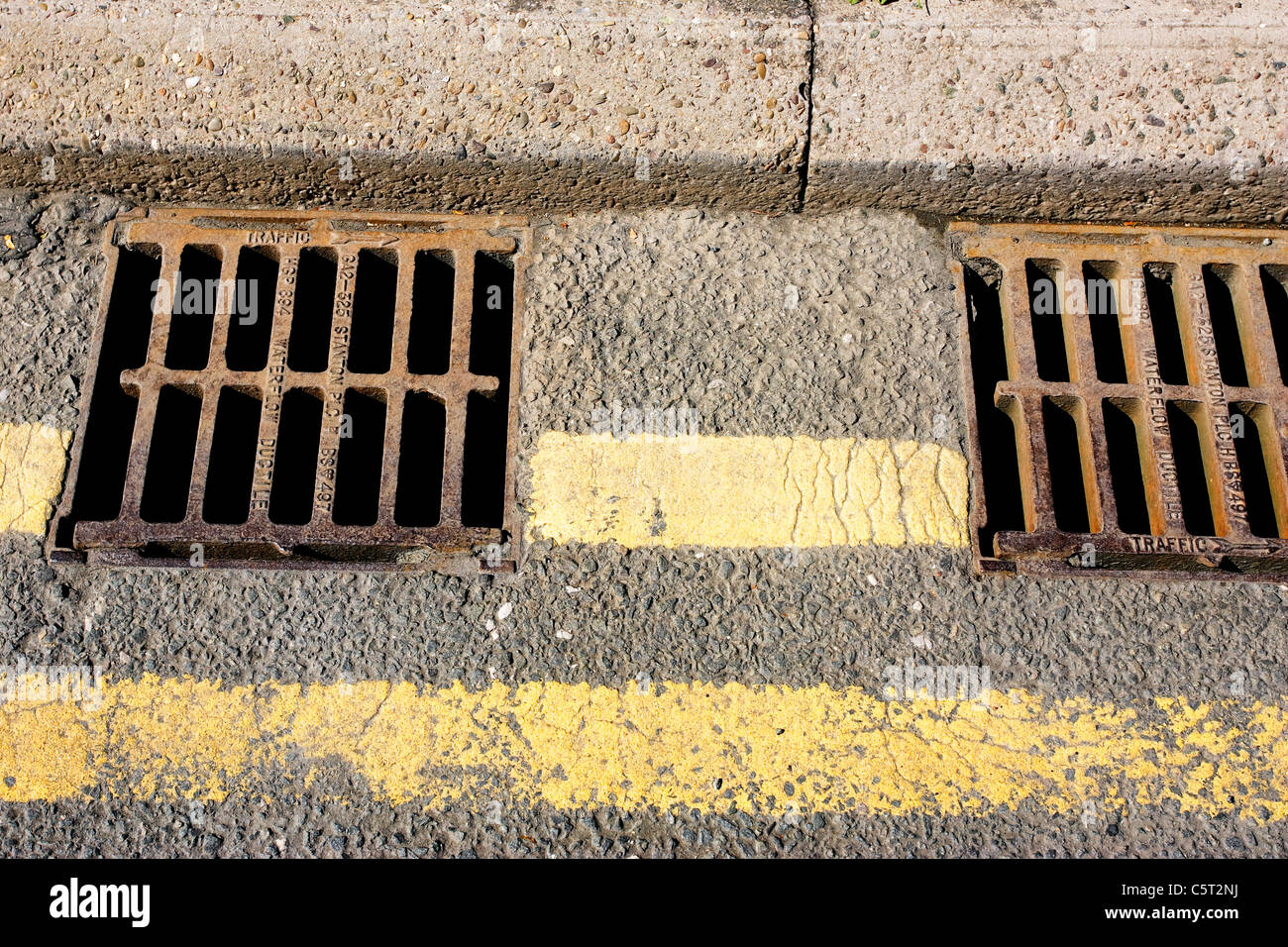 Water drains at the side of a road - Stock Image