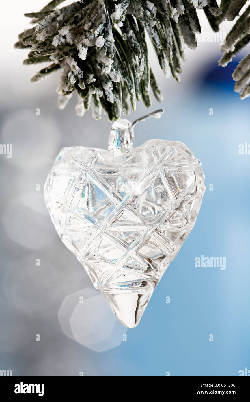 Heart-shaped Christmas tree decoration, on fir branch close-up - Stock Image