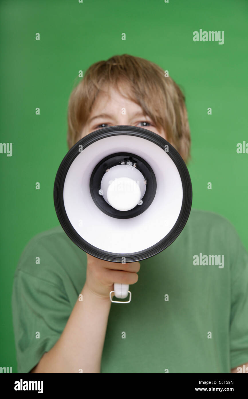 Close up of boy screaming in megaphone against green background - Stock Image