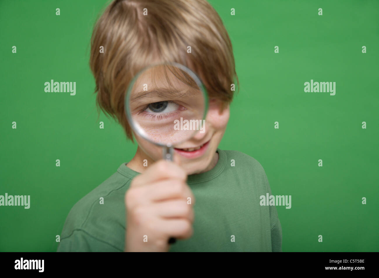 Close up of boy looking through magnifying glass against green background - Stock Image