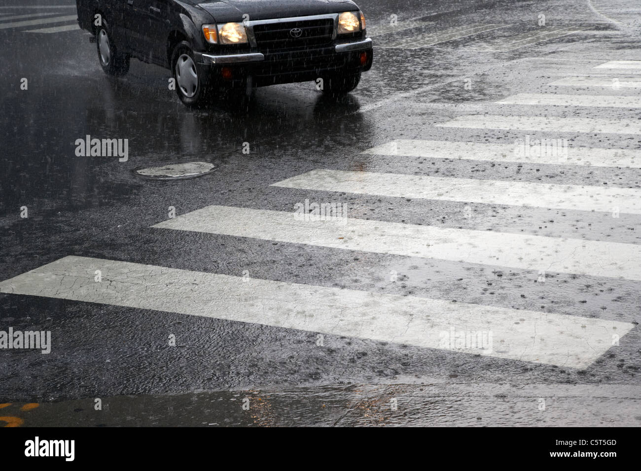 car approaching crosswalk in heavy rain downtown broadway Nashville Tennessee USA - Stock Image
