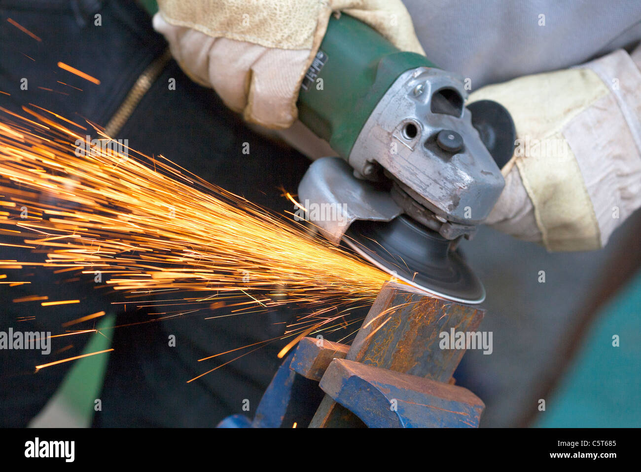 Close up of man sharpening piece of iron with angle grinder - Stock Image