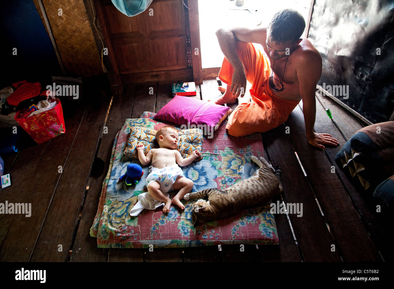 Thailand, Baby and cat sleeping with man sitting - Stock Image