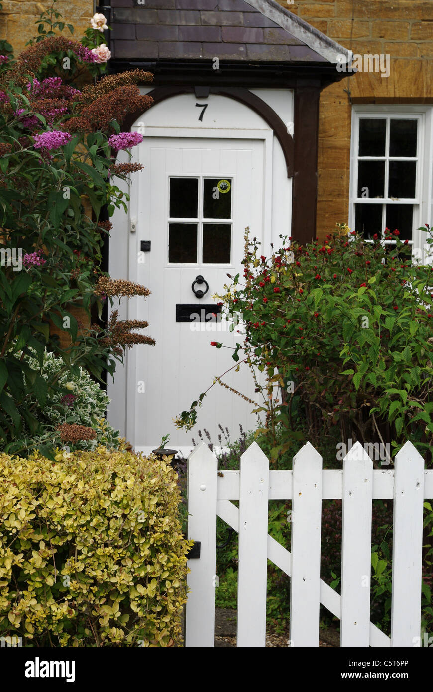White gate and door of a country cottage in the village of Sywell, UK - Stock Image