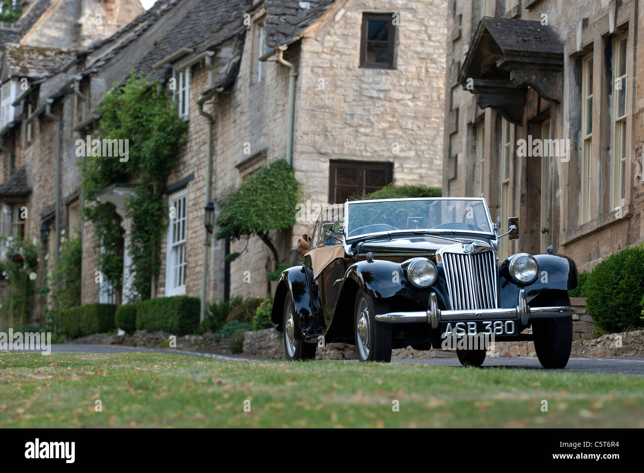 1955  Vintage MG TF 1500 car parked outside houses in the medieval town of Burford . Cotswolds, England - Stock Image