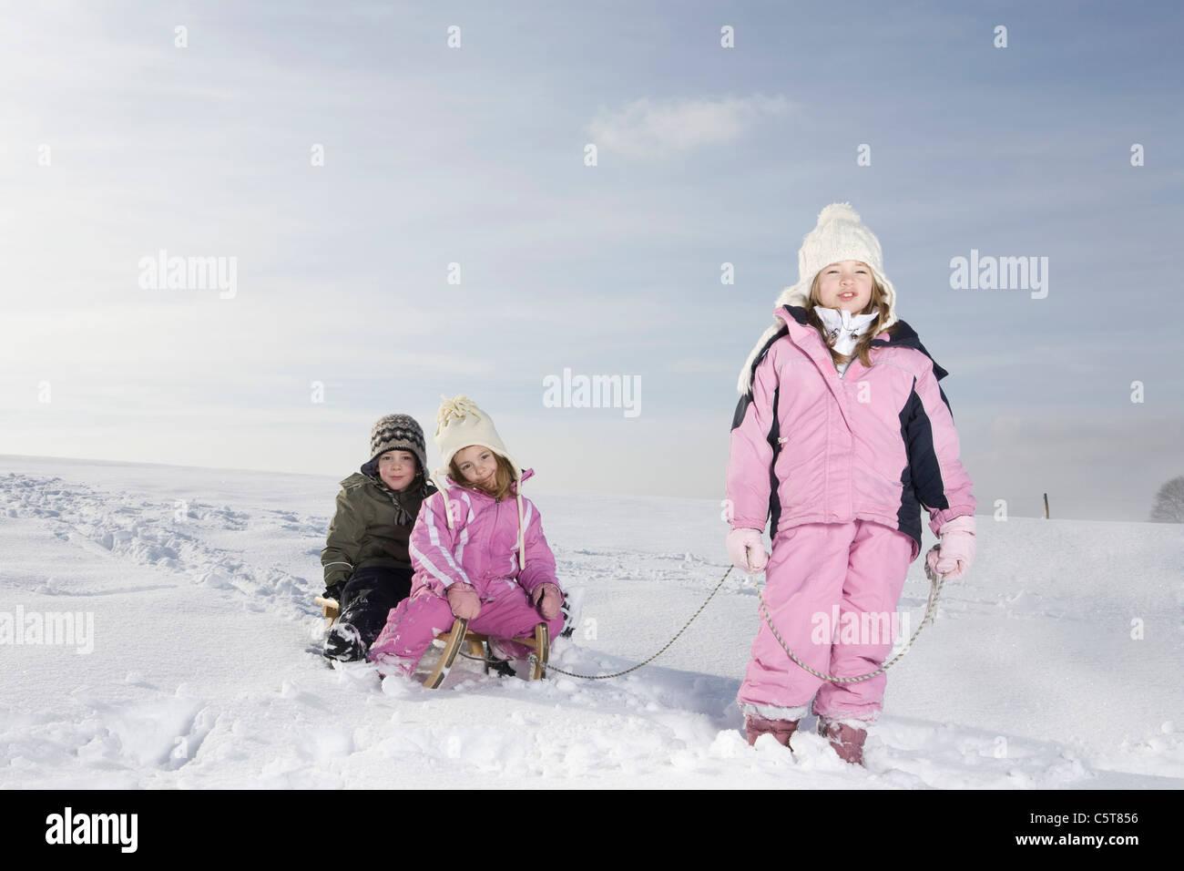 Germany, Bavaria, Munich, Girl (8-9) pulling sledge, portrait - Stock Image