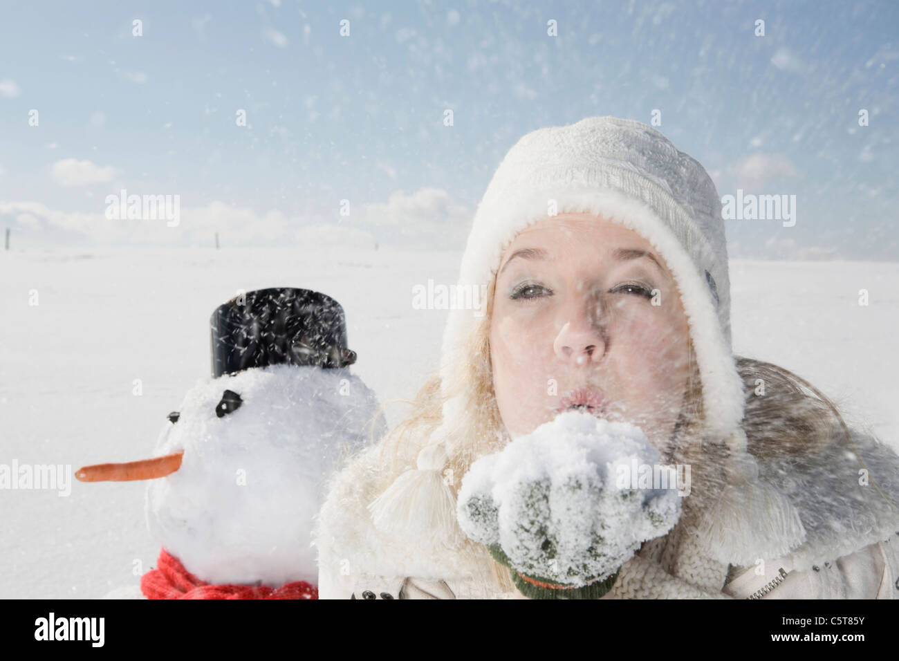Germany, Bavaria, Munich, Young woman blowing snow off hand, portrait - Stock Image