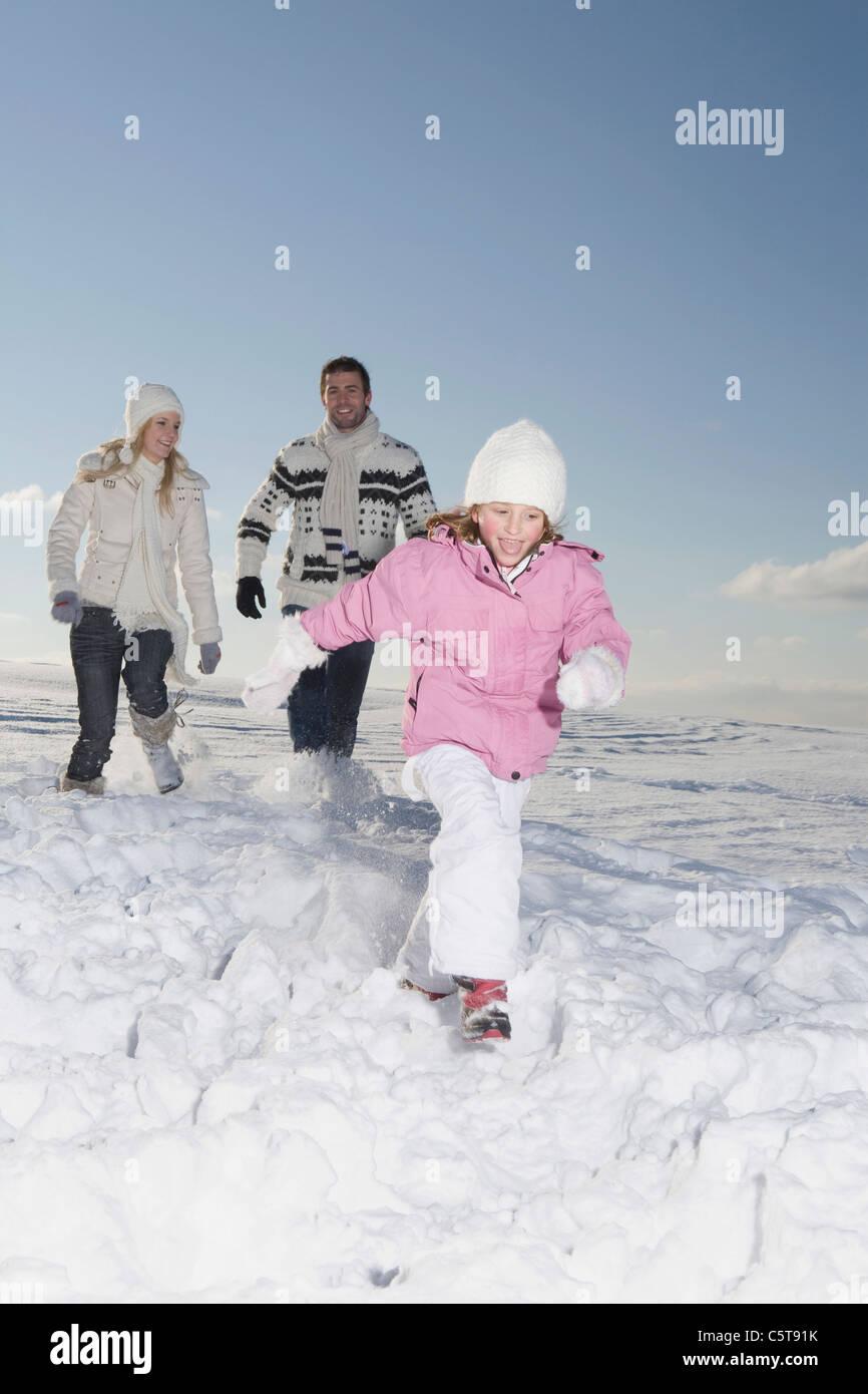 Germany, Bavaria, Munich, Familiy running across  snowy landscape - Stock Image