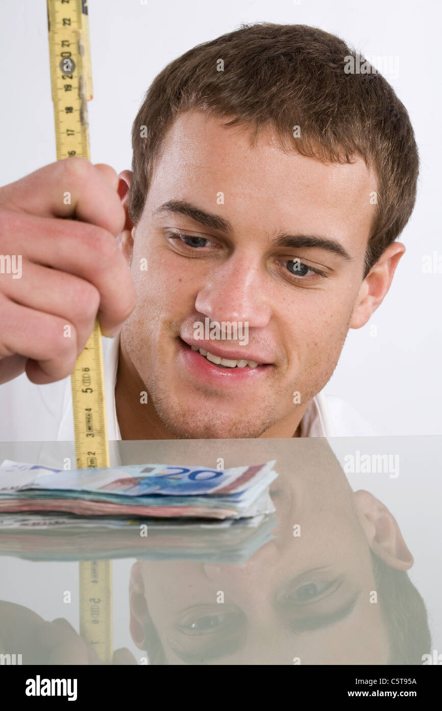 Young man holding folding rule, portrait - Stock Image