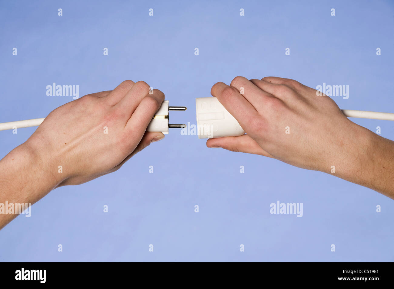 Person holding electrical cord and plug - Stock Image