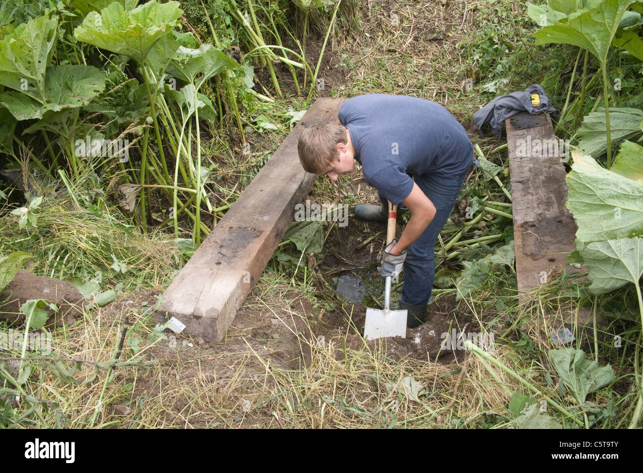 UK Young man digging out foundations to install a sleeper bridge on a public footpath volunteering as part Welsh - Stock Image