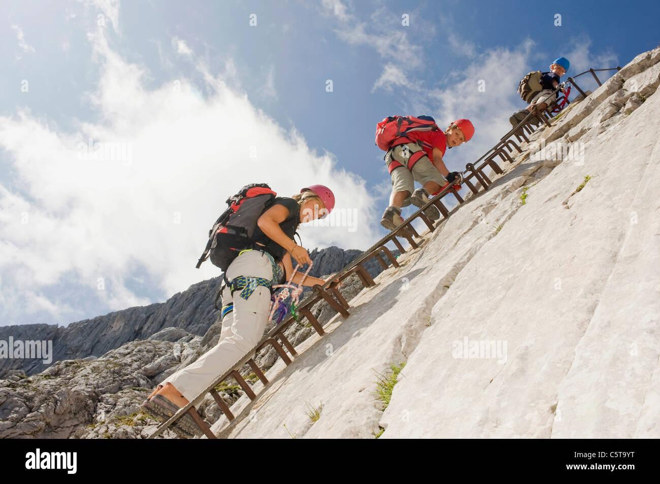 Germany, Garmisch-Partenkirchen, Alpspitz, Mother and sons (10-11), (12-13) climbing rock face on ladder - Stock Image