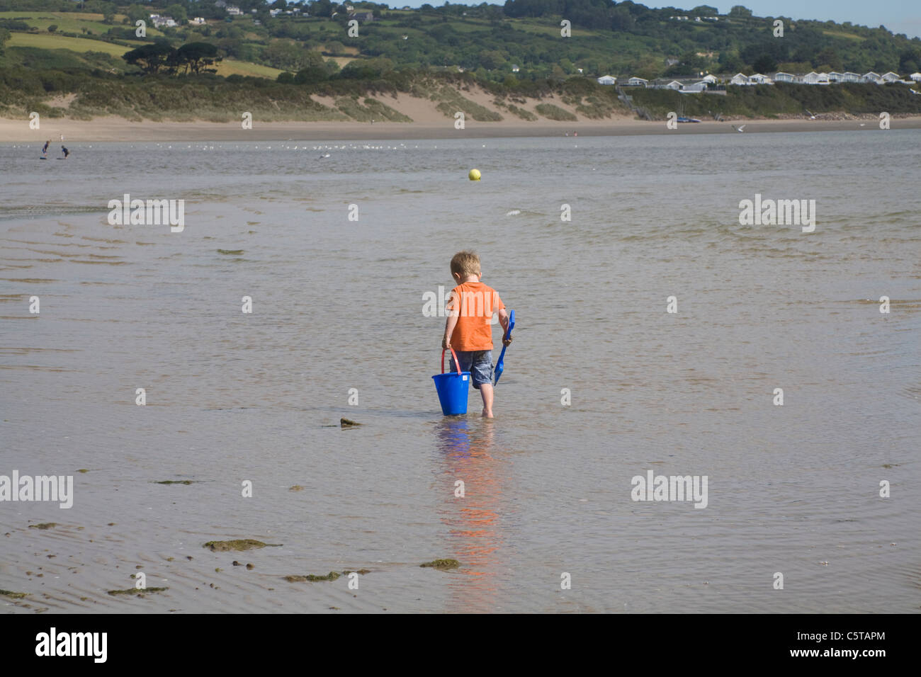 Abersoch Gwynedd North Wales UK Small blonde haired boy paddling in the shallow water carrying a blue bucket and - Stock Image