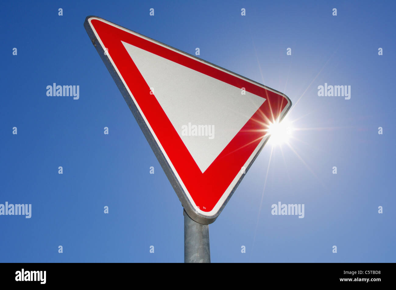 Give way traffic sign against blue sky Stock Photo