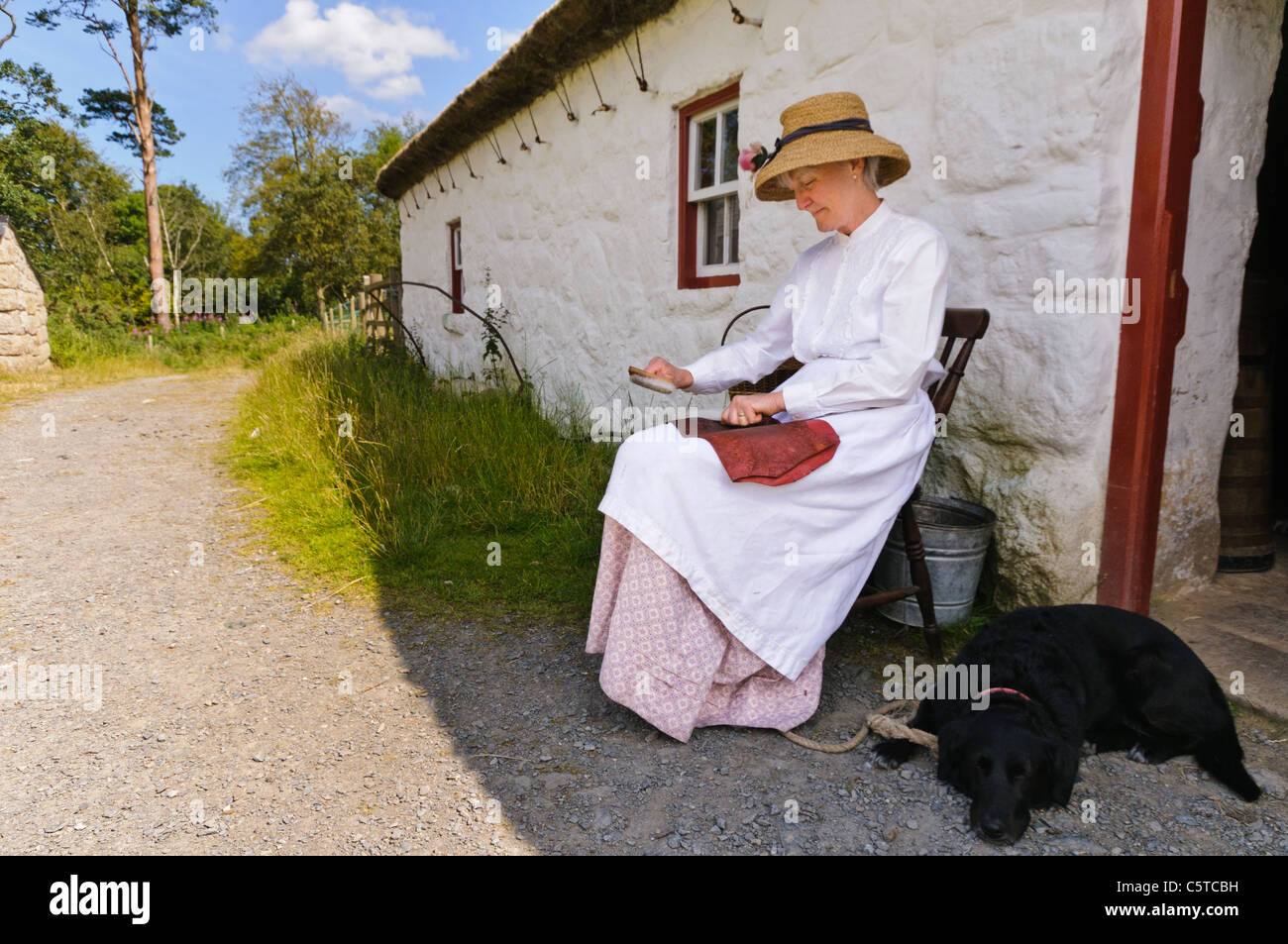 Woman in Irish Victorian dress sitting outside a cottage while 'carding' wool with a metal brush at the - Stock Image