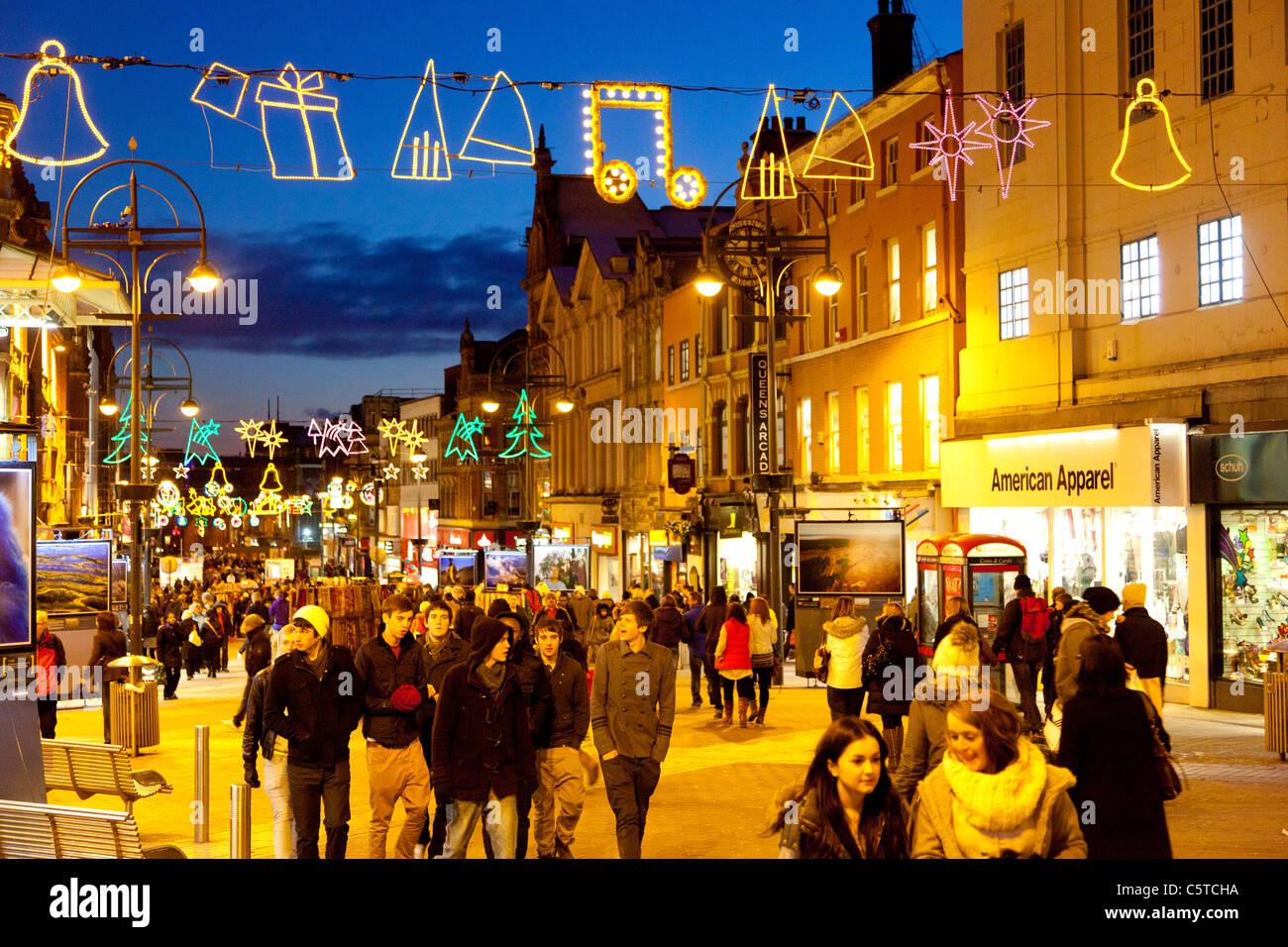 Christmas shopping on Briggate Leeds UK at dusk - Stock Image