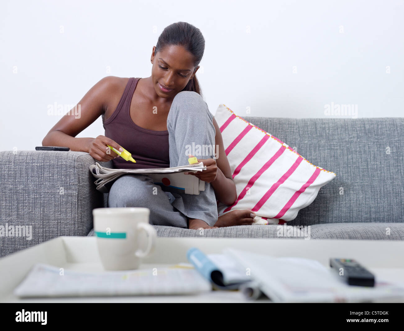 mid adult indian woman on sofa, looking for job offers on newspapers. Front view, copy space - Stock Image