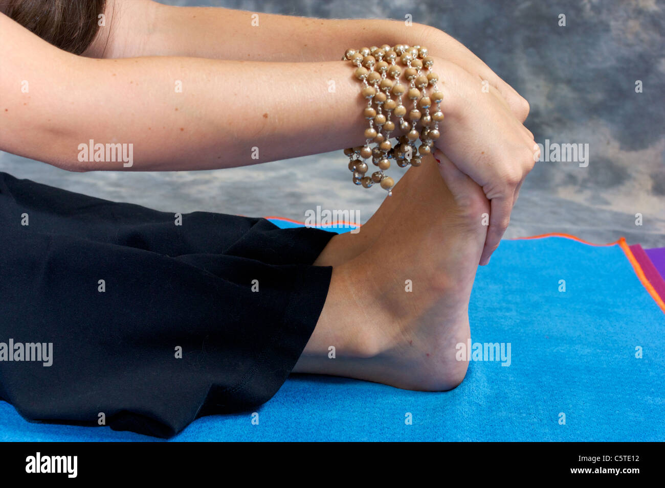 Close up of a woman's hands and feet as she bends over in a yogic forward fold or Paschimottasana on yoga mat - Stock Image
