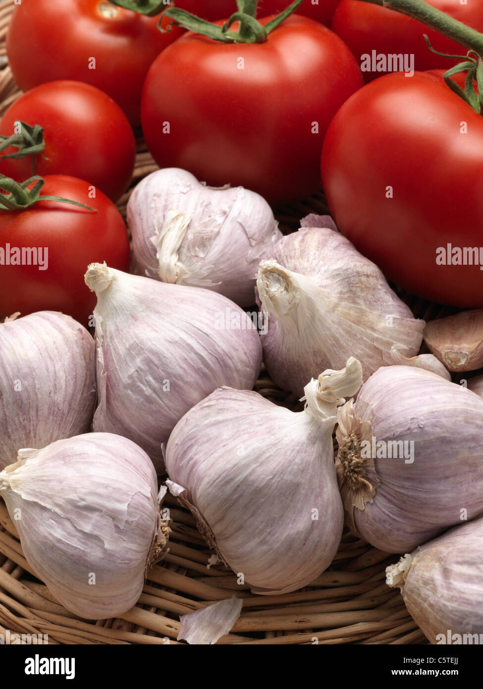 A wicker basket of garlic and ripe red tomatoes - Stock Image