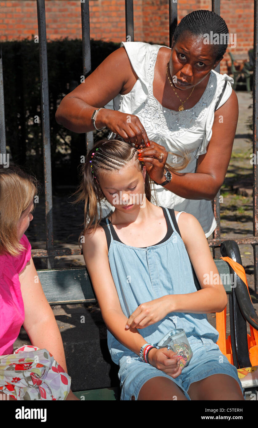 Girl getting micro braids by coloured woman on Strøget, the main pedestrian shopping and entertainment street - Stock Image