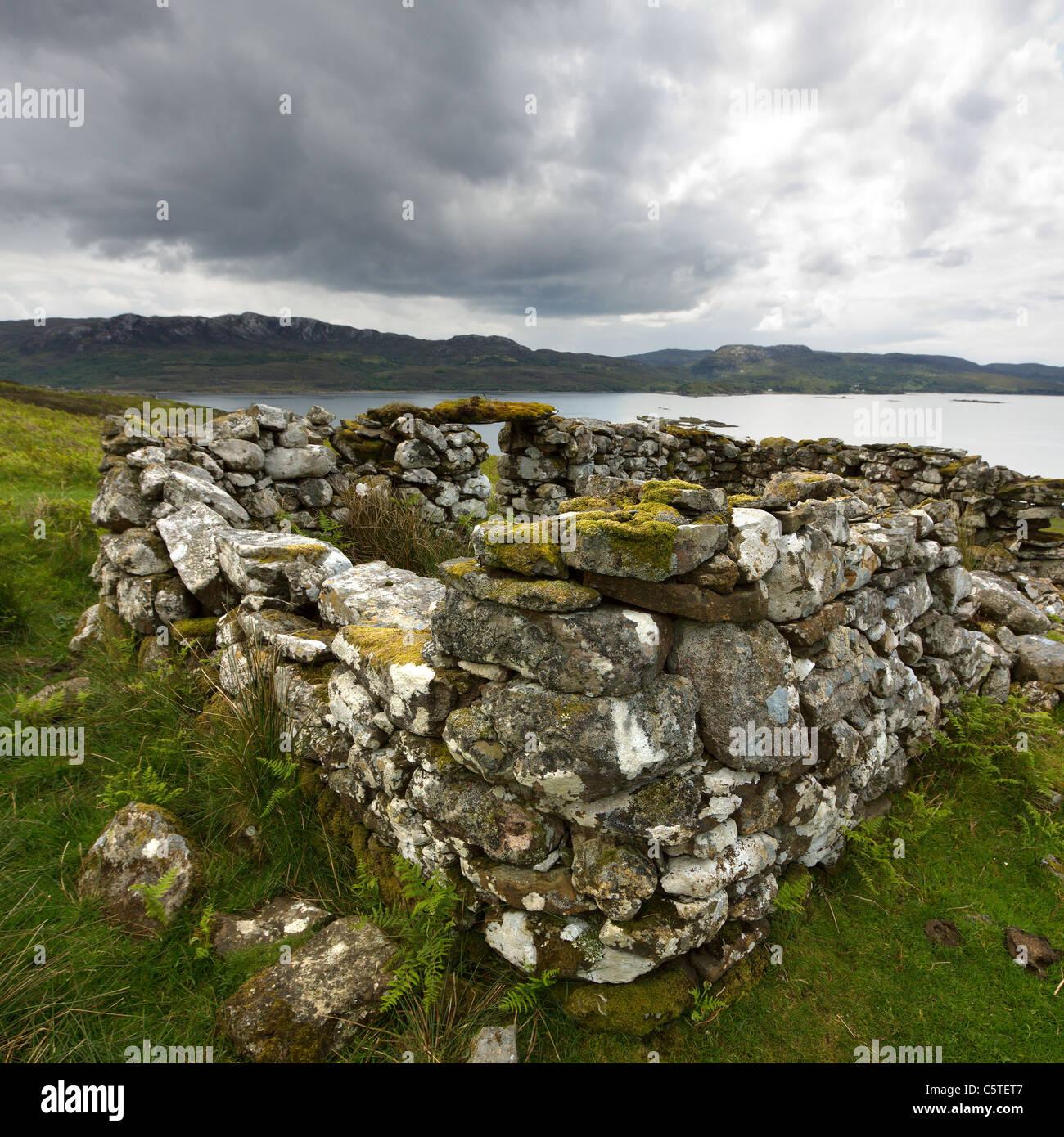 Ruined old croft building with Loch Eishort and Sleat Peninsula beyond, Boreraig, Isle of Skye, Scotland, UK - Stock Image