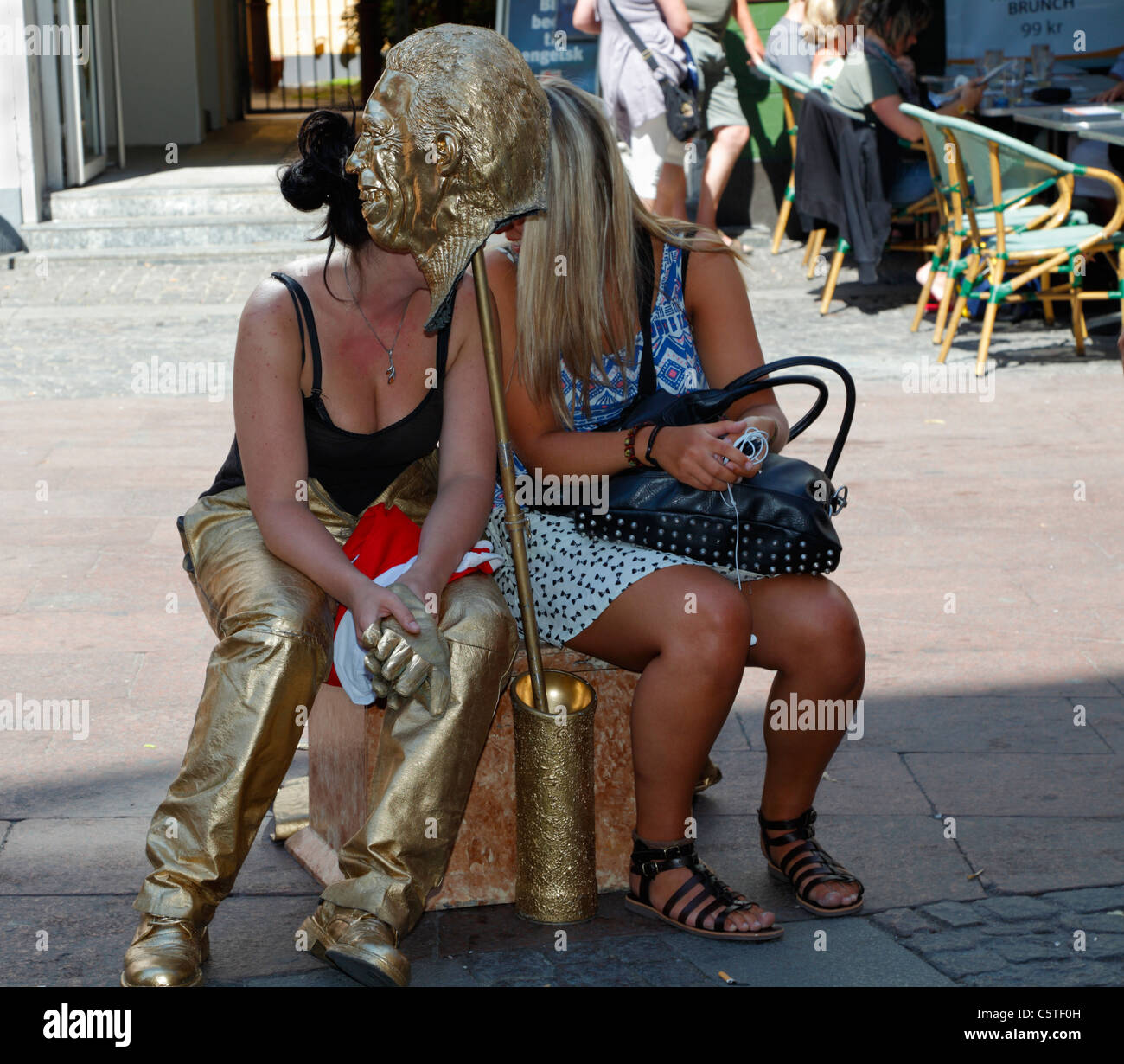 The golden static figure on Stroeget in Copenhagen is a girl - now relaxing in the shade with a friend behind the - Stock Image