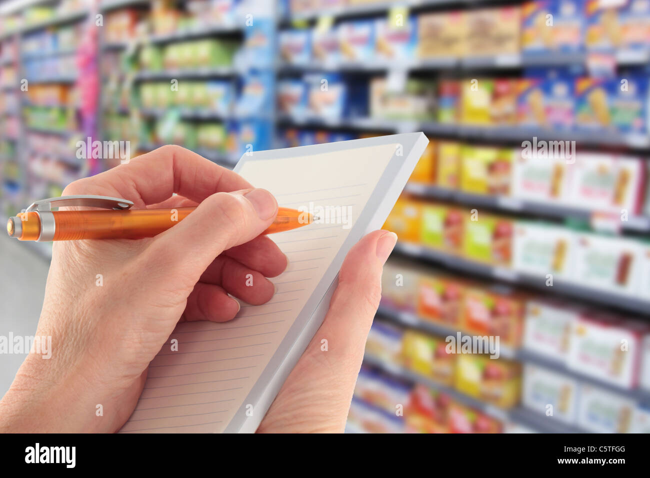 Writing a Shopping List in the Supermarket - Stock Image