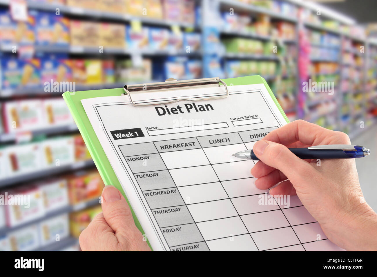 Writing a Diet Plan in the Supermarket - Stock Image