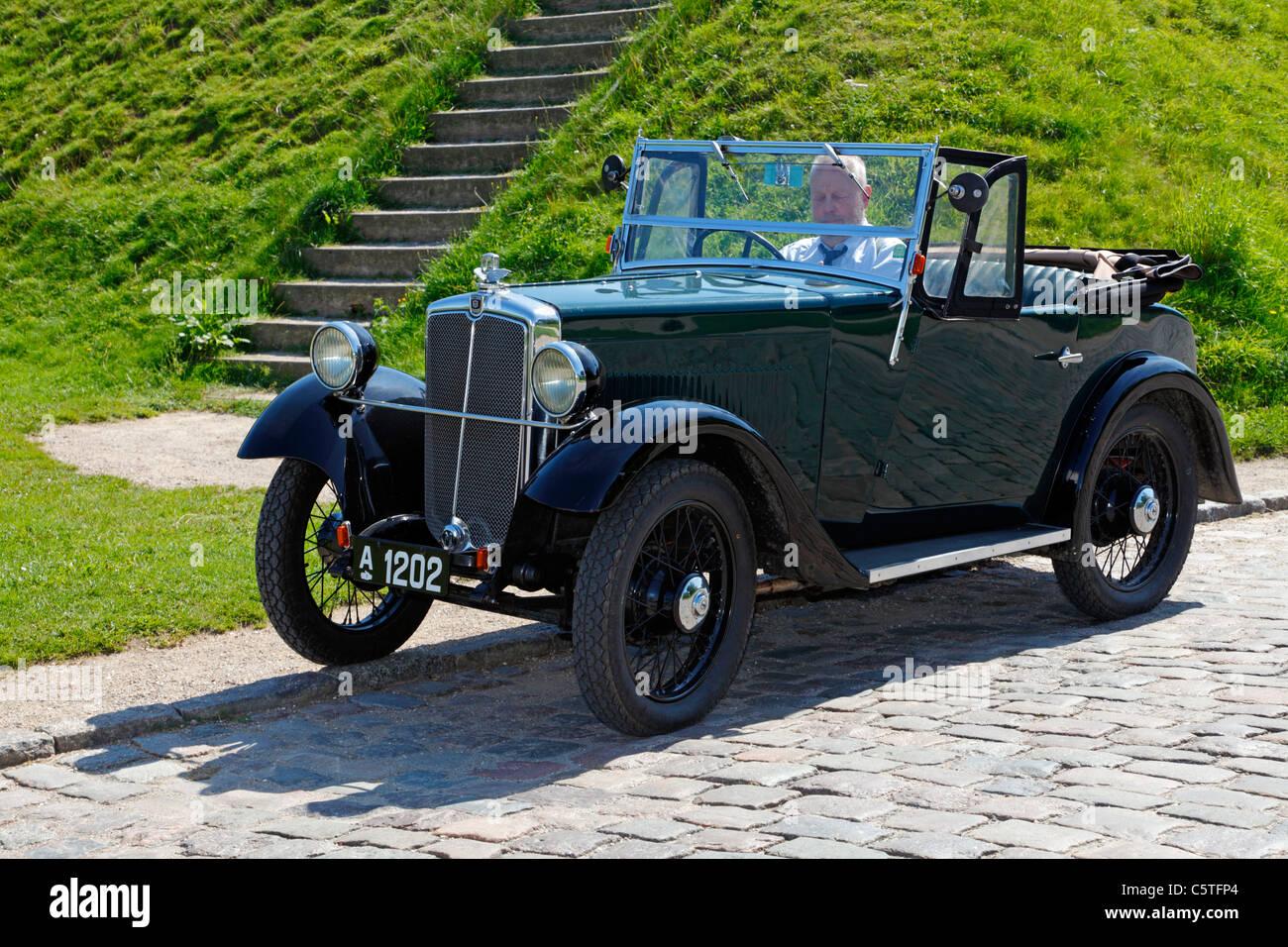 Dark green, vintage Morris Minor car from 1934 at the Citadel in Copenhagen, Denmark, on a warm summer day - Stock Image