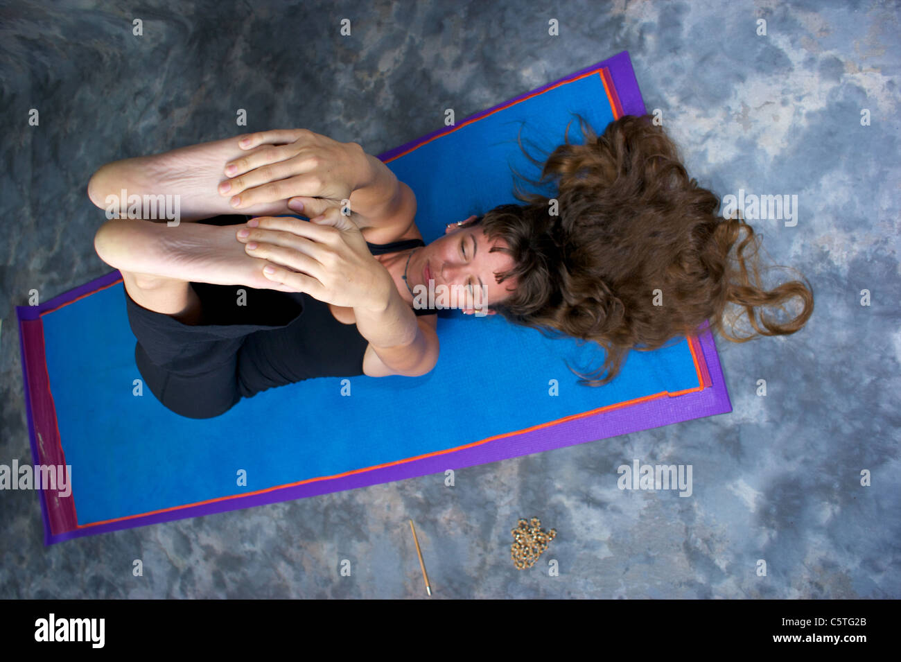 Foreshortened view looking down on attractive long haired woman on yoga mat stretching hamstrings - Stock Image