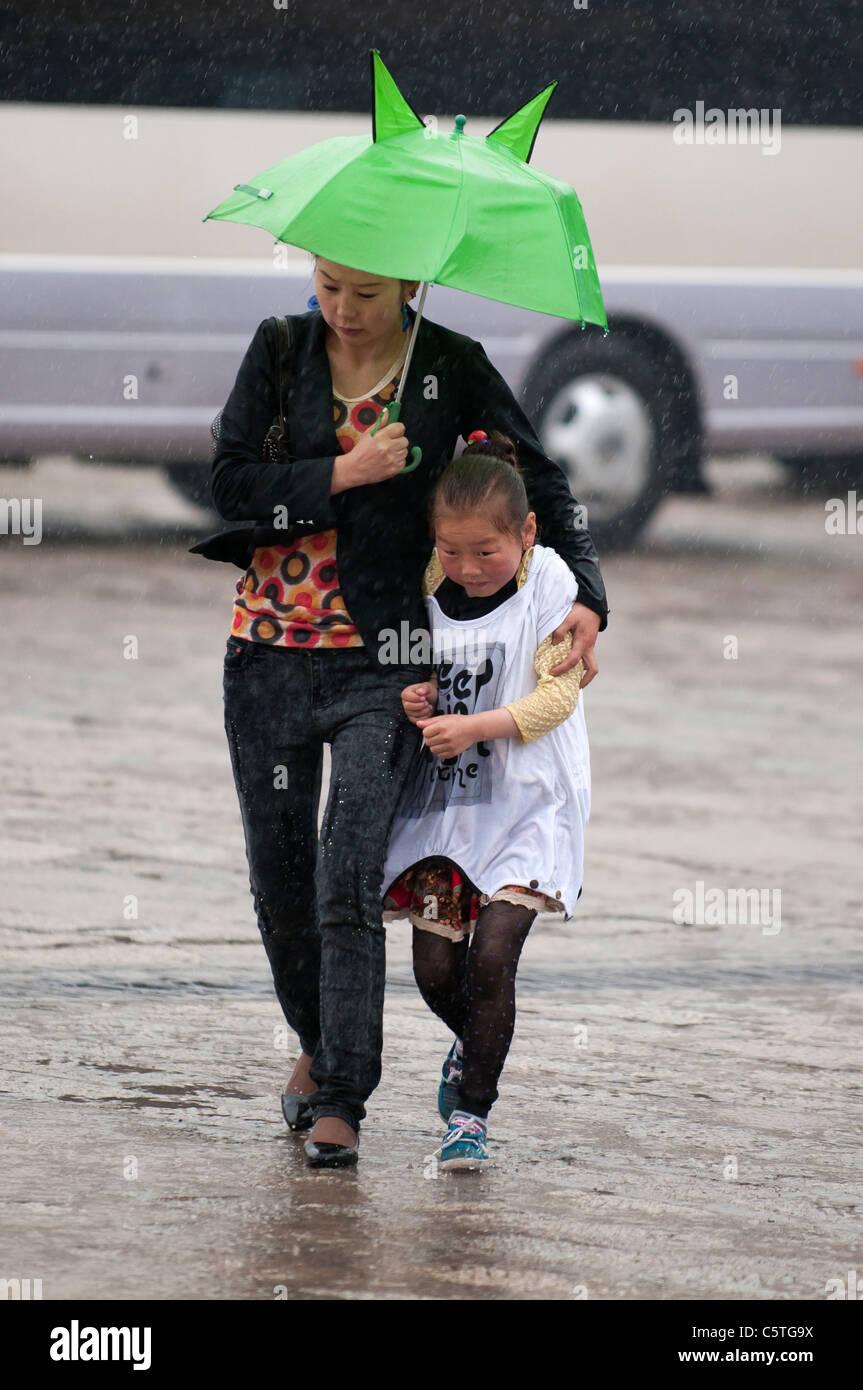 Mother and daughter race through rain at Kumbum Monastery, Huangzhong, Qinghai Province, China - Stock Image