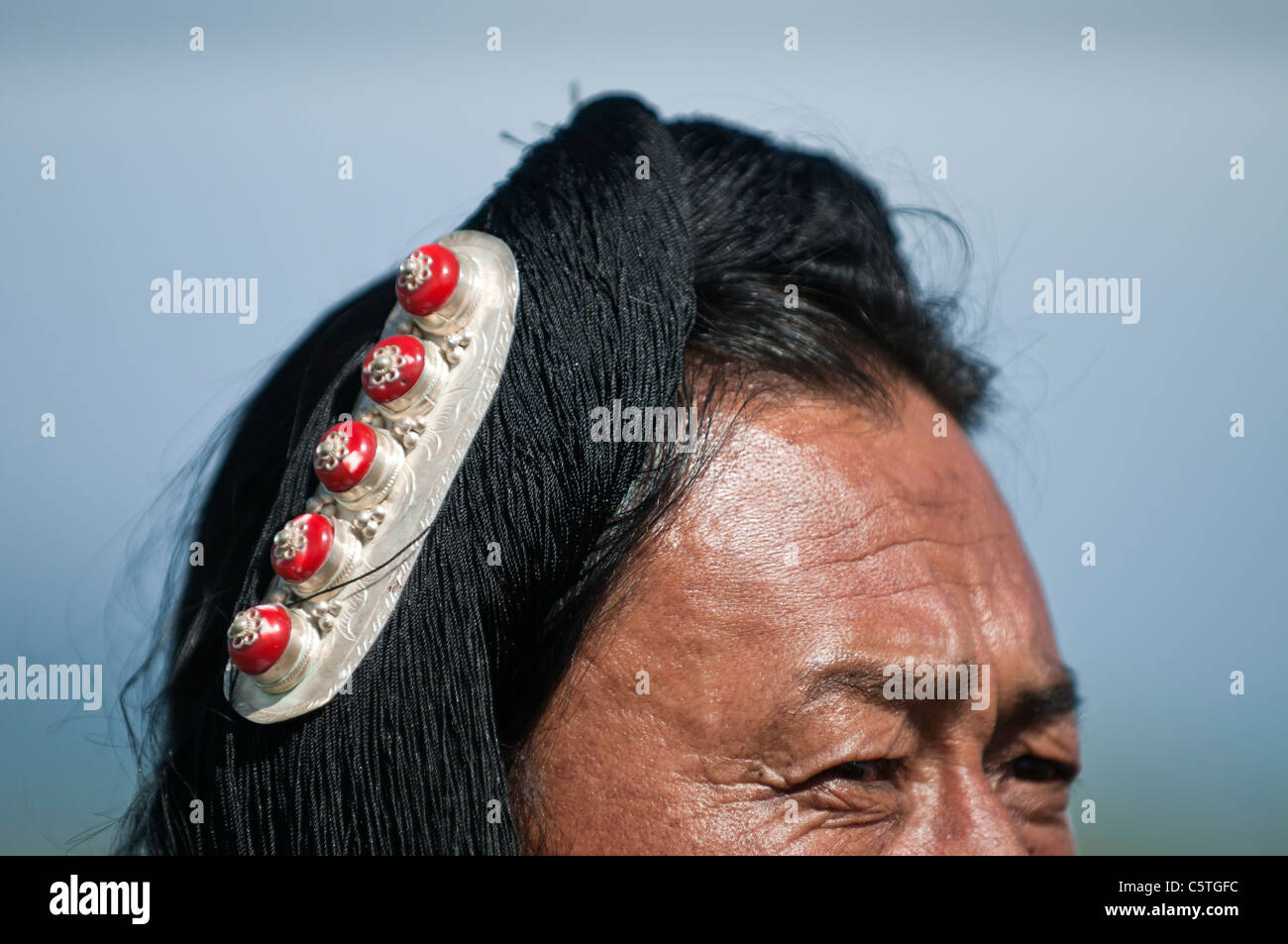 Wearing a silver hair piece, an ethnic Tibetan man attends folk festival, Haibei, Qinghai Province, China - Stock Image