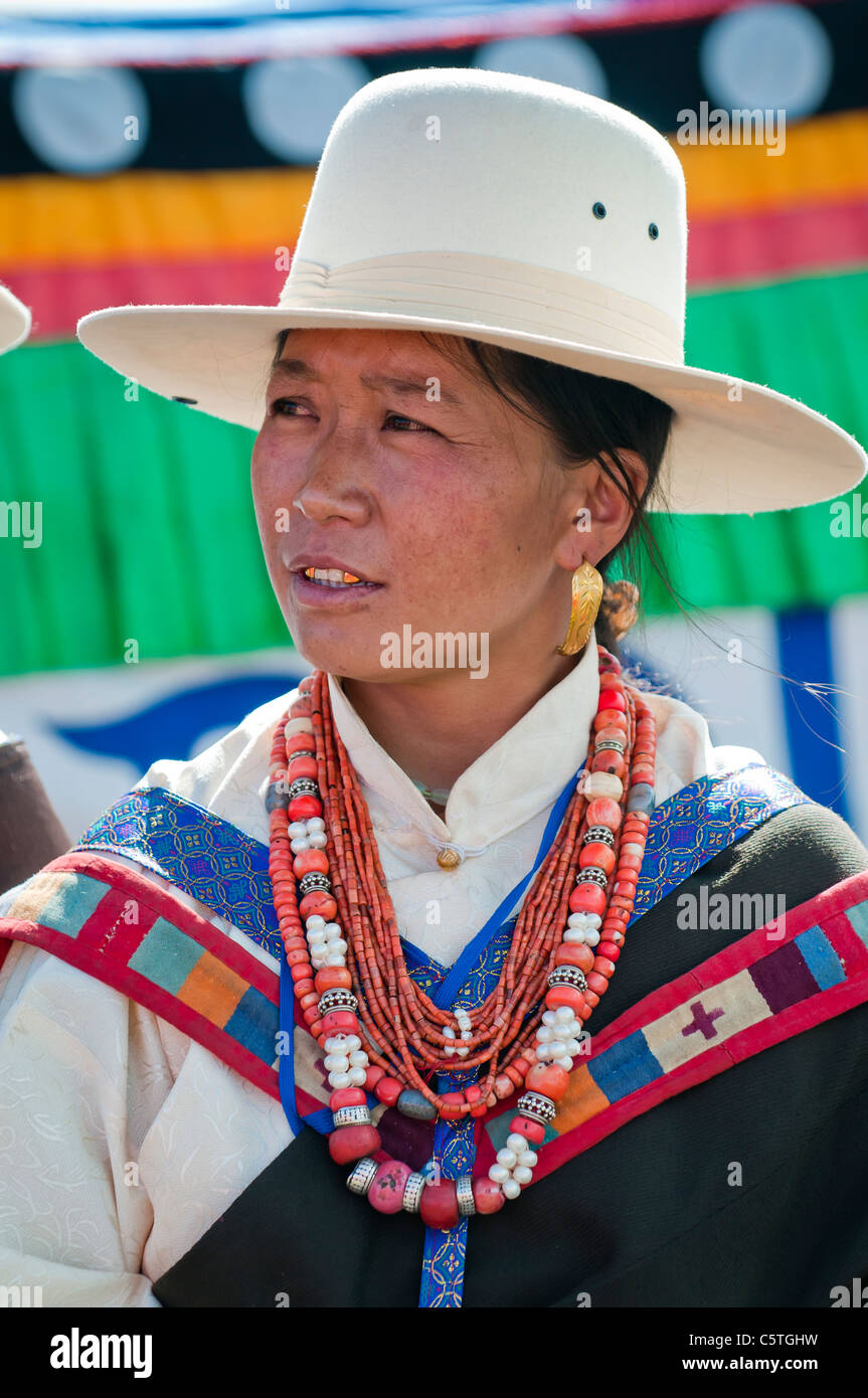 Dressed in traditional ethnic Tibetan dress, woman waits turn to sing at folk festival, Haibei, Qinghai Province, Stock Photo
