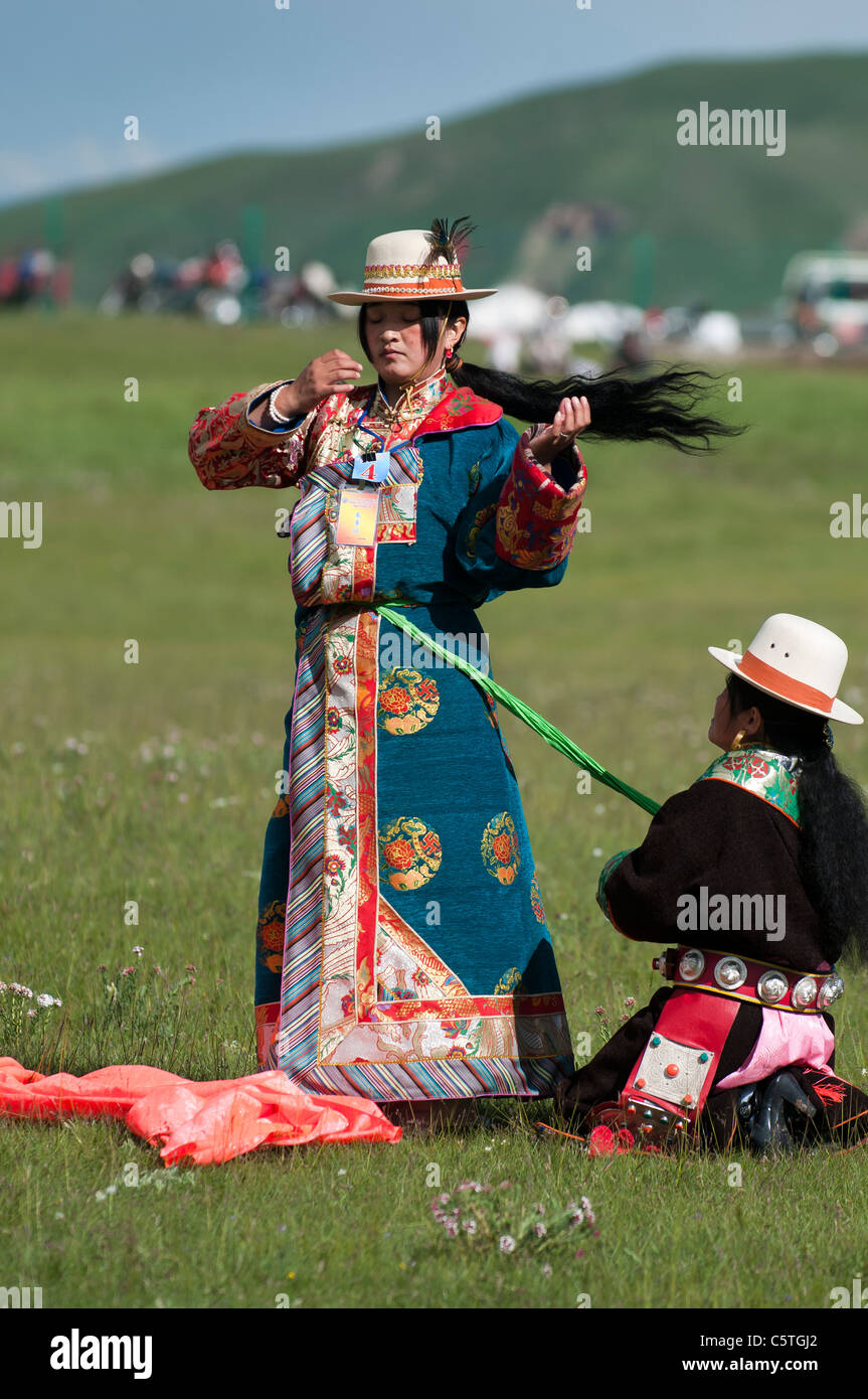 Dressed in traditional ethnic Tibetan dress, woman prepares costume to sing at folk festival, Haibei, Qinghai Province, - Stock Image
