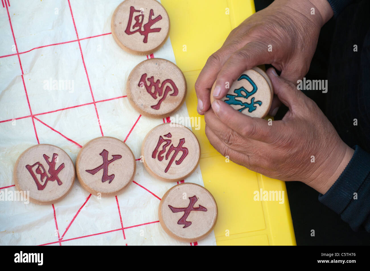 Player holds game pieces during Xiangqi, or Chinese chess, at outdoor cafe, Quilian, Qinghai Province, China - Stock Image