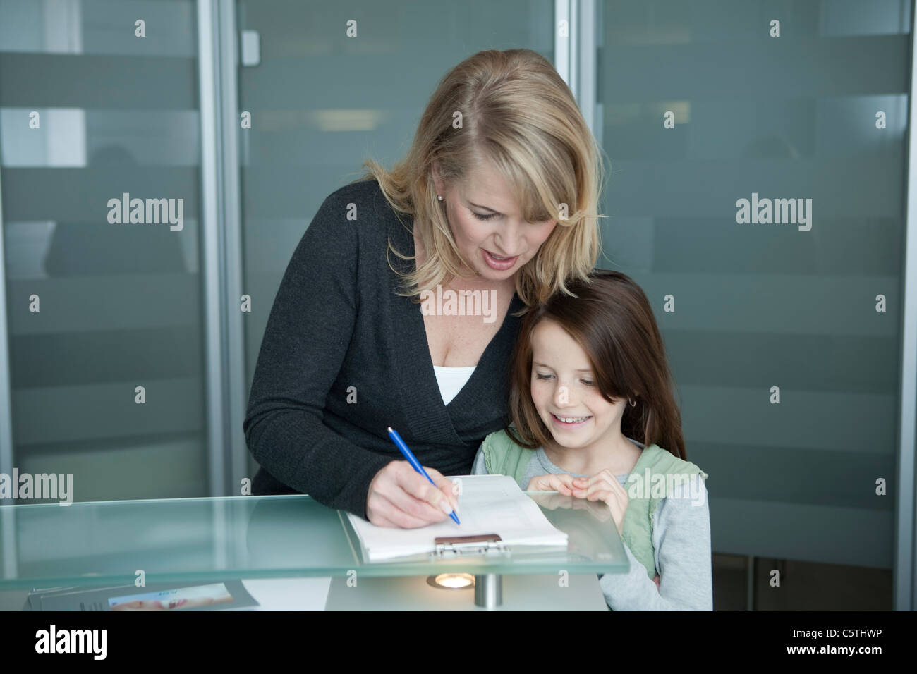 Germany, Bavaria, Landsberg, Mother and daughter (8-9), Mother filling out form at clinic reception - Stock Image