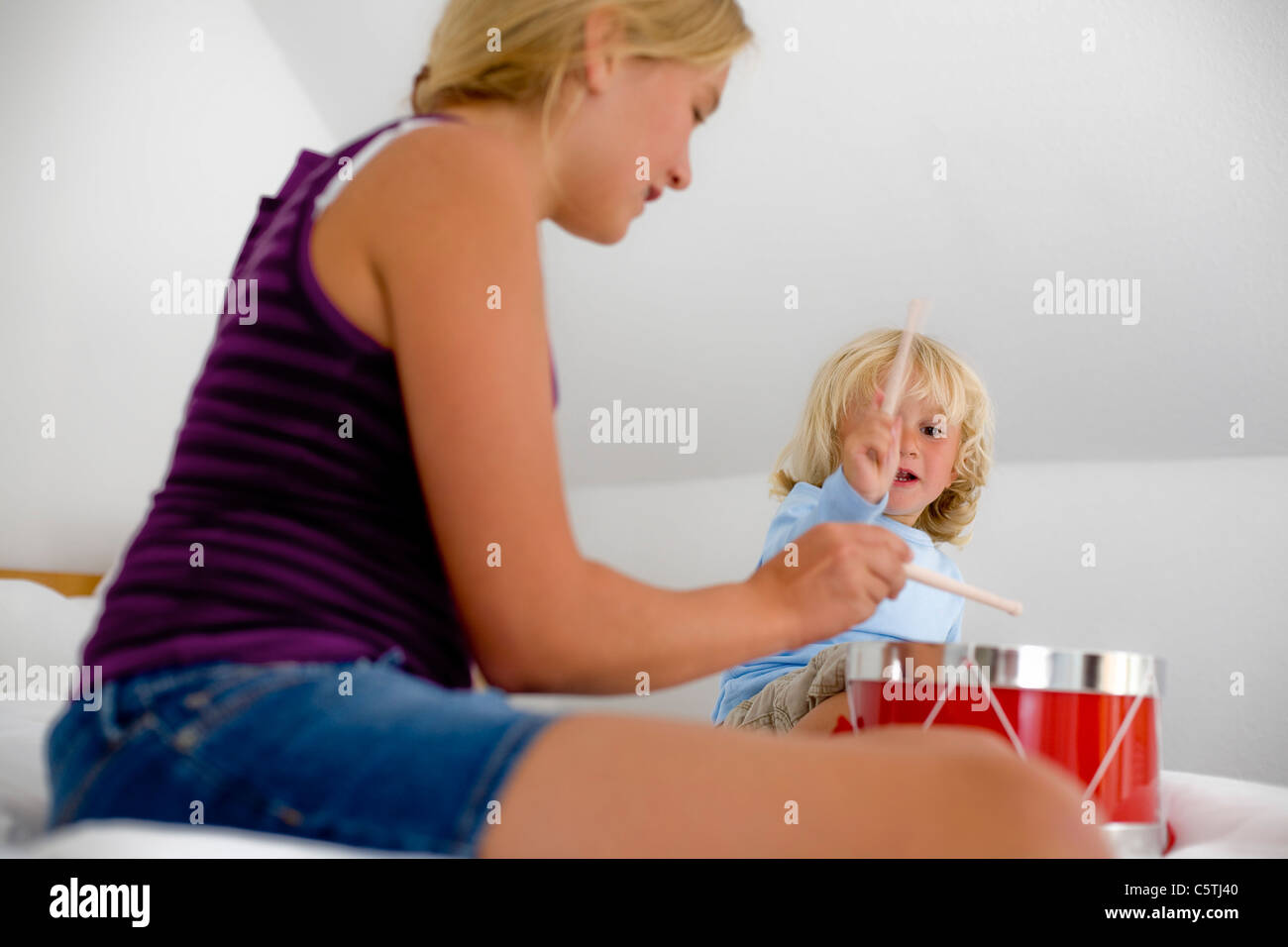 Germany, Ammersee, Diessen, Girl (12-13) and boy (2-3) playing with drums - Stock Image