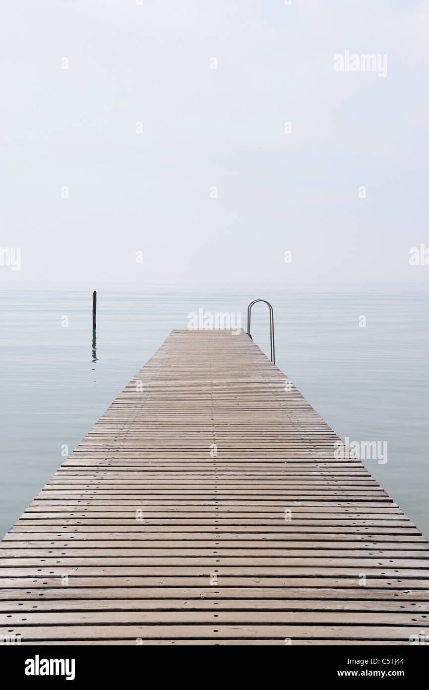 Italy, Jetty on Lake Garda with mist - Stock Image