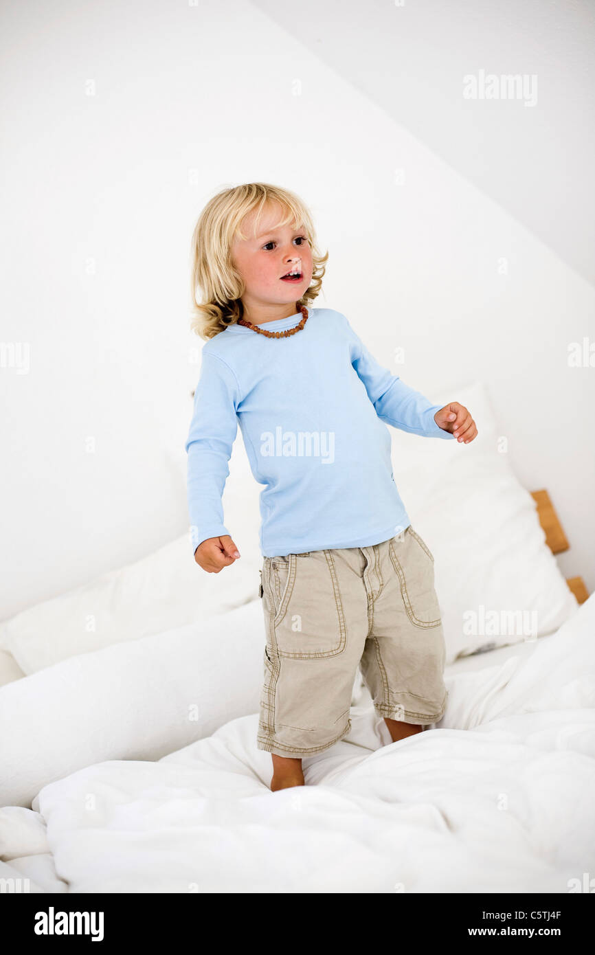 Germany, Ammersee, Diessen, Young boy (2-3) standing on bed - Stock Image