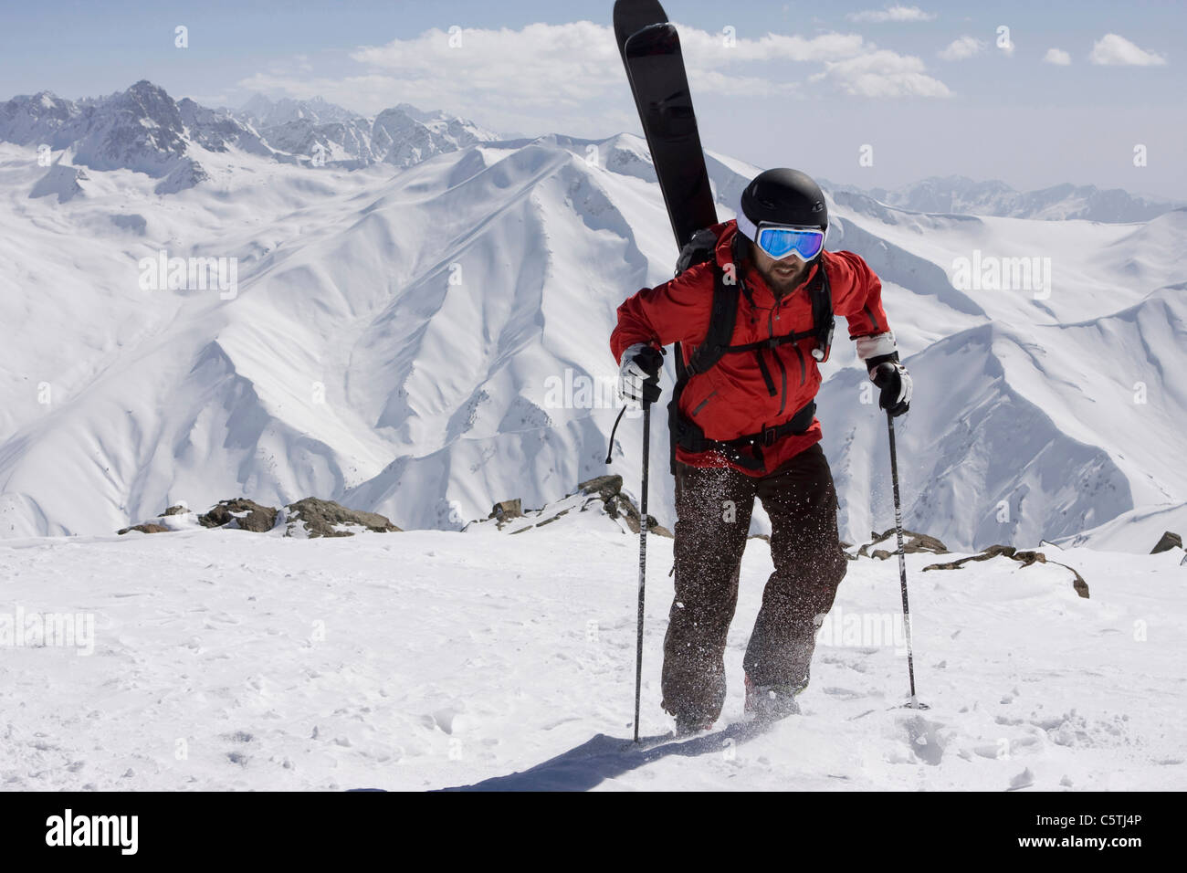 India, Kashmir, Gulmarg, Man with skis on back going uphill - Stock Image