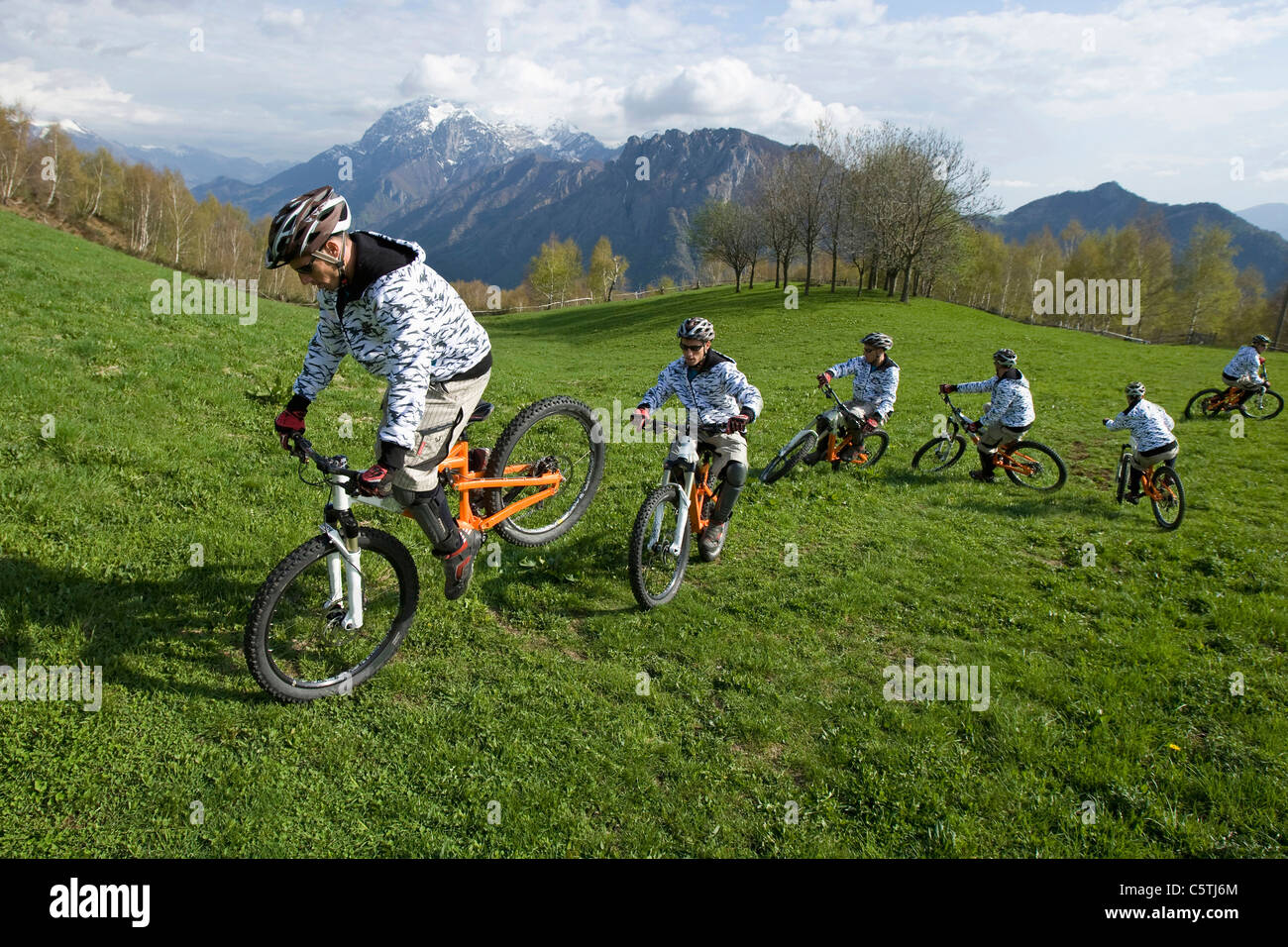 Italy, Lake Como, Group of mountain bikers riding across meadow - Stock Image
