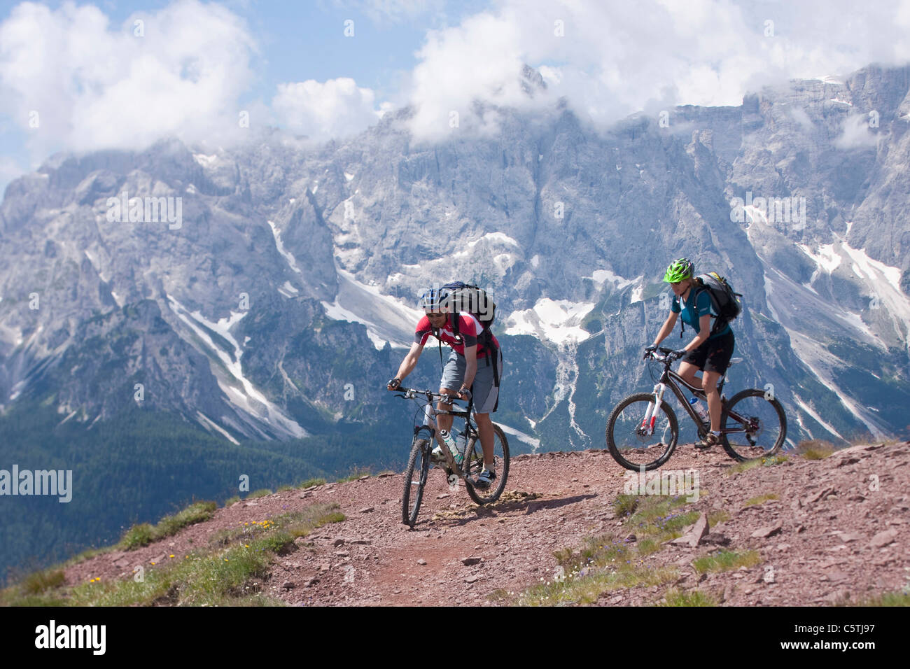Italy, Dolomites, Couple mountainbiking - Stock Image