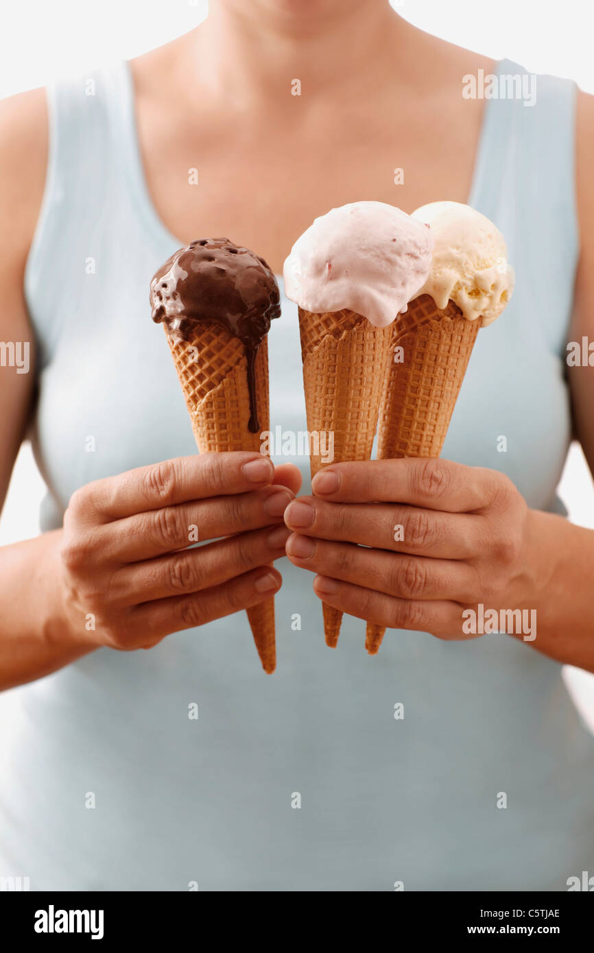 Woman holding different ice creams, upper section, close-up - Stock Image