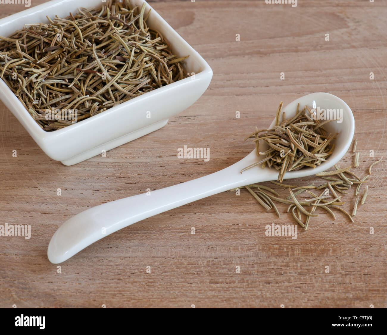A Spoon and Dishful Of Dried Aromatic Rosemary Leaves, Up On A Wooden Work Surface - Stock Image
